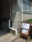 京都イタリア会館地階のギャラリー「Space Alternative(スペース・オルタナティブ)」の入口階段上に置かれた「胡羌鬲絶展」の案内板