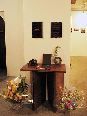 京都市左京区のギャラリー「スペースオルタナティブ」で開かれた高潔(Gao Jie)の写真展「恒河少年」の記帳台と贈答品の草花飾り