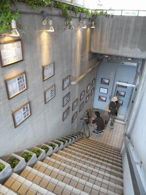 高潔(Gao Jie)写真展「恒河少年」会場へと続くエントランス階段部と格好いい自転車に見入る高潔とYK