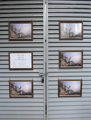 スペースオルタナティブ入口の階段下、扉前壁面に掲げられた高潔(Gao Jie)写真展「恒河少年」の案内掲示
