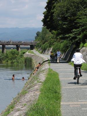 猛暑日の京都・賀茂川(鴨川)で泳ぐ子供たちと、河岸をゆく自転車