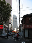 よくある町並みの奥に高層ビル聳える上海の朝