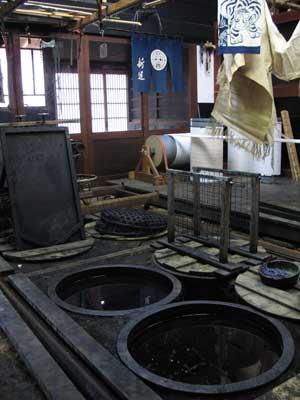 土間床の甕に天然藍染料が貯留される、京都府美山町の「ちいさな藍美術館」1階の新道弘之氏の工房