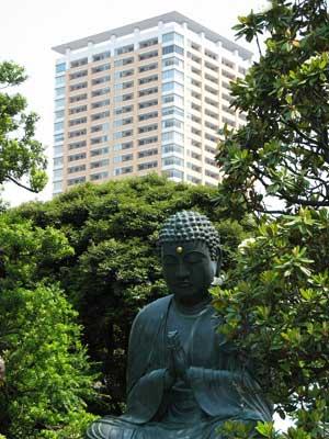 日暮里駅裏の高台上にある天王寺の佛像と、背後に聳える駅前高層マンション