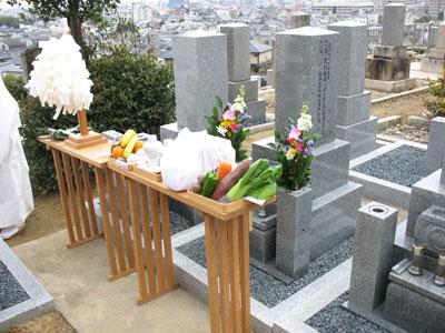 大幣(祓串)や供物が飾られる神道特有の八足台が置かれた、納骨式最中の墓前