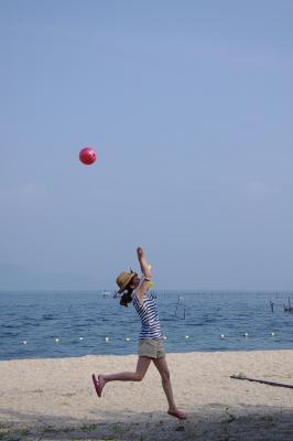 琵琶湖西岸・近江舞子の浜で、大きく逸れたビーチバレーのボールを後ろ向きに打ち返す女子