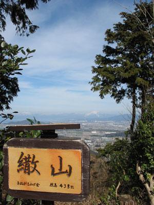 繖山(観音寺山)山頂の標識と、湖東平野や雪を戴く伊吹山の眺め