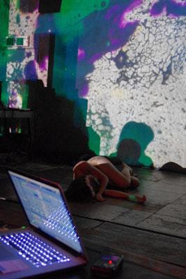 京都市街東部・木屋町のライブハウス「UrBANGUILD(アバンギルド)」のライブイベント「fake JuNkroom vol.1」で、クリストファー氏の機材PCと仙石氏の生映像背景の間に倒れ込む、舞踏演技中のケイトリン(Caitlin)さん