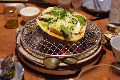 京都市街東部のアパートで行われた忘年会の暖房兼調理器具の七輪と、それに対応して天板に穴がある卓袱台、そして調理中の手づくりピザ
