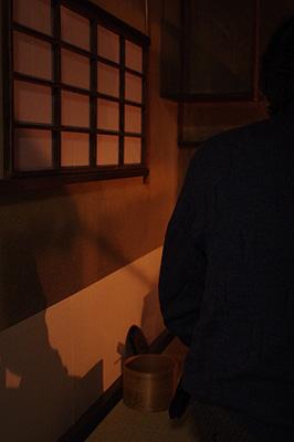 蝋燭の明りに手前座で杓をとる亭主の影が浮かぶ、京都市街東部の国指定文化財茶室の内部