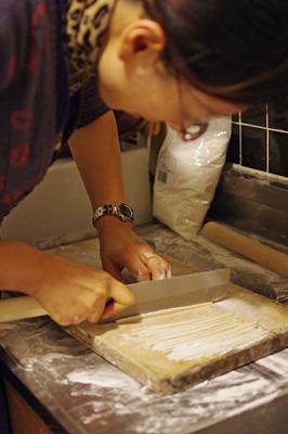 旧暦大晦日に京都市街東部の町家で行われた「忘年新年会」で、慎重に手打ち蕎麦を切るIさん