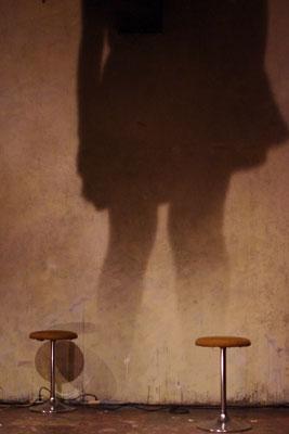 京都市街のライブハウス「UrBANGUILD」のステージに置かれた椅子と壁面に映る大きな人影