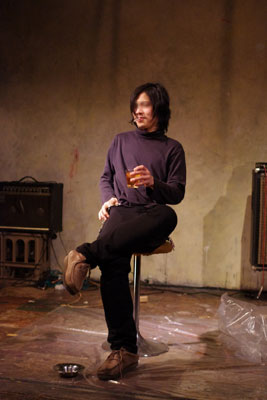 京都市街のライブハウス「UrBANGUILD」で行われた「Dodo」のライブ終了後、椅子に座り煙草と洋酒を味わうベーシストのK君