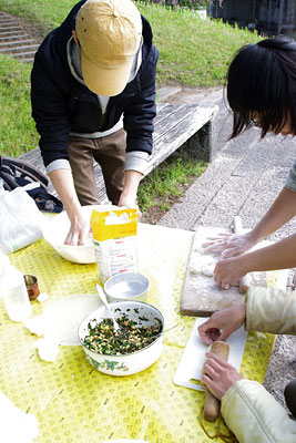 京都・賀茂川(鴨川)のベンチ上で、包子の伸し作業と餡の包み作業を行う麺会一同