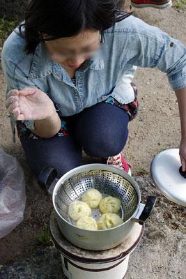 京都・賀茂川(鴨川)の河原に置いた七輪上の鍋蓋を開け、蒸しあがった「包子」を確認し笑顔を見せるモンゴル系中国人のSさん