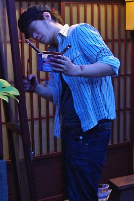 ベンガラ(弁柄・紅殻)と松煙(油煙)を煮亜麻仁油(ボイル油)で溶いた手作り天然塗料で、町家玄関の木製格子戸の古色塗りを行う塗会参加者