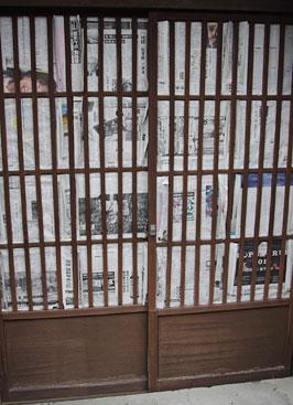 古色塗り作業に備えガラス部分を新聞で養生した、塗装前の町家玄関の格子引戸