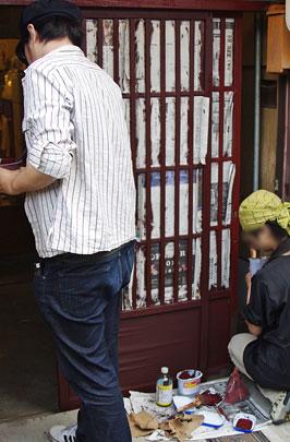 古新聞でマスキングした町家玄関の格子戸に手作り天然塗料で古色塗りを施す塗会参加者