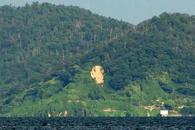 滋賀県琵琶湖西岸の近江舞子雄松浜から見た、対岸沖島の旧採石場辺りの崩落箇所