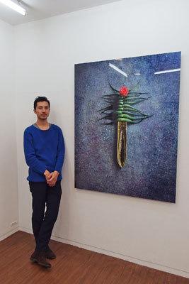写真展「FLOWERS」が開催されている、大阪中之島裏の古ビルギャラリー「白(gallery HAKU OSAKA)」の一室で、美麗かつ艶っぽい生け花作家・杉田一弥氏作品とのコラボ作の前に佇む写真家・来田猛君