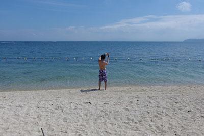青い空と湖面広がる、滋賀県琵琶湖西岸の近江舞子・雄松浜でスマホ撮影に興じる初参加者のT君