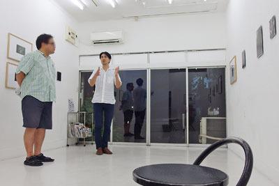 京都蹴上のギャラリー「アートスペース虹」で開かれた来田猛個展「光の輪郭」で、お客さんの問いに応じる来田君
