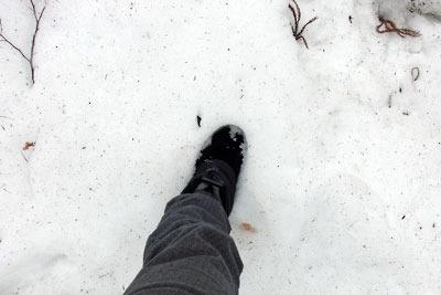 京都市街北部・北山山中の花脊峠路肩の残雪に沈むブーツ足