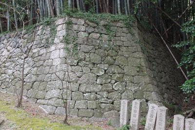 頂部に京都・石清水八幡宮がある男山中腹の、参道脇に続く神宮寺子院跡平坦地縁の、「隅切り」が施された石垣端部