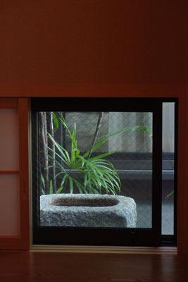 茶室開きが行われた京都市街東部の知人宅茶室の躙窓(にじりまど)から見える、露地の蹲(つくばい)