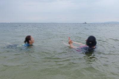 滋賀県琵琶湖西岸の砂浜湖岸で大浴場的に湖水を楽しむ、湖会参加者の二人組