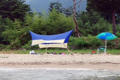 滋賀県琵琶湖西岸の砂浜湖岸に設営された、日除けのタープやパラソル・椅子等の湖会拠点