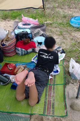滋賀県琵琶湖西岸の砂浜湖岸でのひと泳ぎ後に、流行りの「任天堂スイッチ」を楽しむ湖会子供参加者