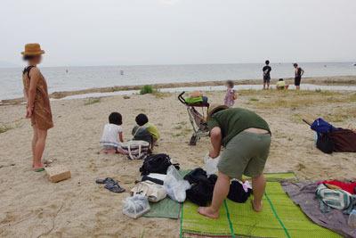 夕方、滋賀県琵琶湖西岸の砂浜湖岸で、拠点撤収の準備をする湖会参加者ら