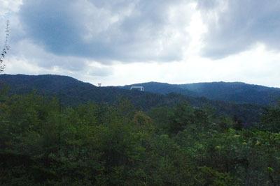 雪村展が行われた、滋賀県東南・信楽山中のミホミュージアム(miho museum)美術館棟の窓から見えた山中の教団施設(中央の屋根等)
