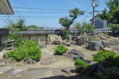 京都市街南郊の旧巨椋池内の堤防集落「東一口」に残る旧山田家住宅の、奇岩・貴石が多く使われる主屋北側の庭園