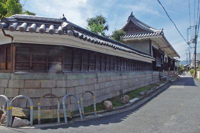 京都市街南郊にある、旧巨椋池内の堤防集落「東一口」のなかで威容を誇る、旧山田家住宅の長屋門と切石積みの漆喰塀