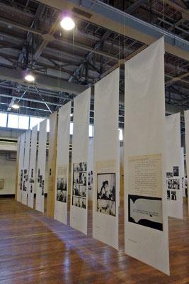 新聞用ロール紙に印刷され会場に吊るされる、ロバート・フランクの「ブックス アンド フィルムス、1947-2017 神戸展(Robert Frank, Books and Films, 1947-2017 in Kobe)」の写真作品及び解説