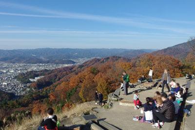 ハイカーで賑わう大文字火床中心部からみた山の紅葉と京都市街