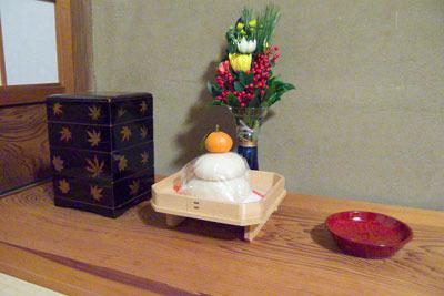 床の間の正月飾りの鏡餅や重箱・漆器・花