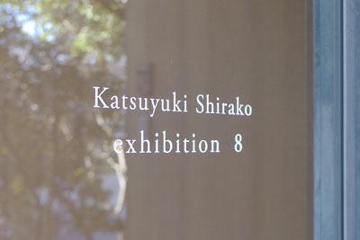 円山公園内のギャラリー「eN arts(エンアーツ)」の玄関窓に記された白子勝之個展「exhibition 8」の文字