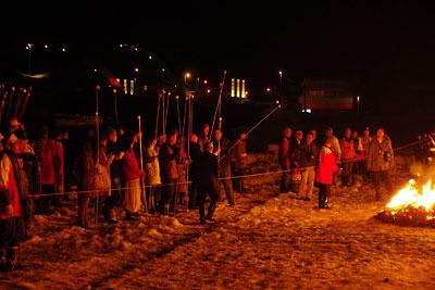 福井県勝山左義長祭のどんど焼きの火の傍で棒の先に餅を付けて控える人々