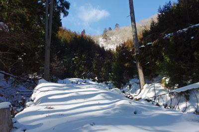 急斜の隘路上部に残る緩傾斜の道跡と京都市街北部の旧花脊峠方向に広がる空