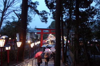 京都・吉田神社の石段下を上る傘さす参拝者と、鳥居外側に続く節分祭の露店