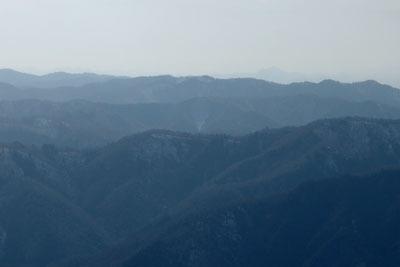 滋賀県比良山脈南部山上からみた、雪が戻った京都・雲取北峰と彼方の笠形山(兵庫中部)