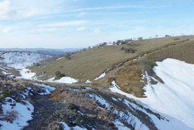 滋賀県比良山脈南部にある、雪残る小女郎峠(中央の鞍部)と小女郎ヶ池