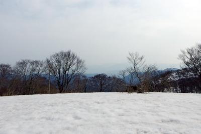 三重嶽山頂に広がる残雪と遠く霞む湖西の山々