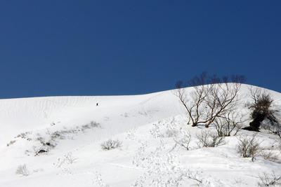 残雪被る岐阜県北部の能郷白山と奥宮方向からトラバースして下る人