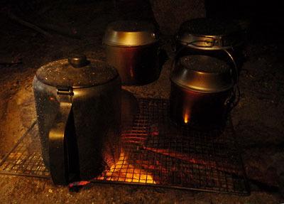 ご飯や汁物等の容器が並ぶ、滋賀県湖南アルプス太神山中での夜の焚火炉端