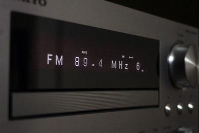 ステレオコンポの表示部に浮かぶ、佐藤弘樹氏担当番組「α-MORNING KYOTO(アルファモーニング京都)」とその放送局「FM-KYOTO,α-STATION(アルファステーション)」の周波数「89.4MHz」