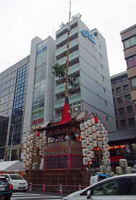 京都・祇園祭の山鉾「函谷鉾」西側の四条通にある雨下の山鉾「月鉾」と背後のビル